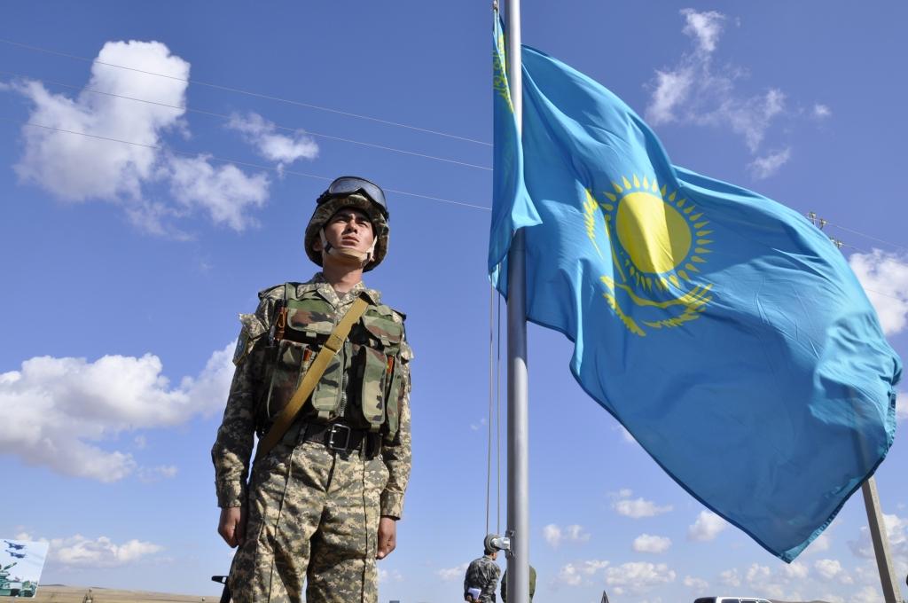 Военный у флага Казахстана